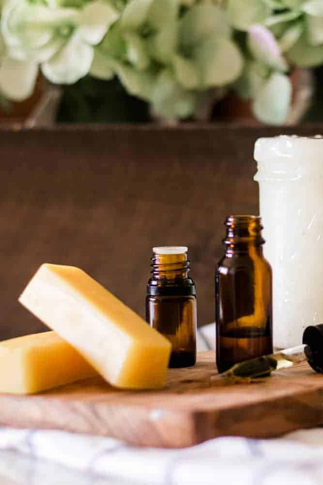 Beeswax, coconut oil, vitamin E oil, and essential oils sitting on wooden board.