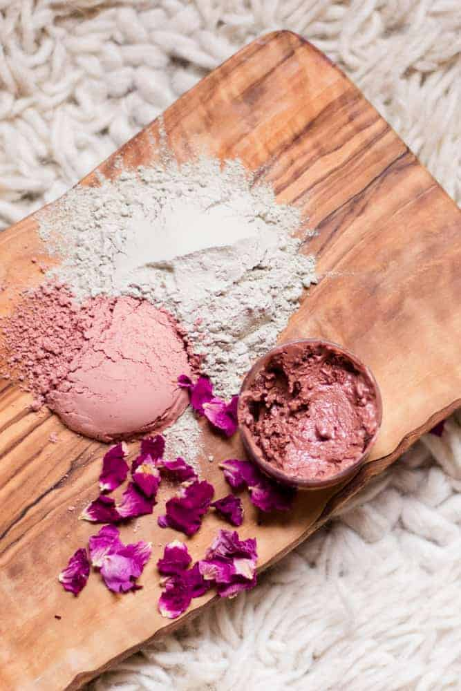 Rose clay, bentonite clay, and rose petals on wooden board with a homemade rose clay face mask in small glass container.
