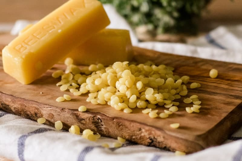 Beeswax pellets and beeswax bars on wooden board.