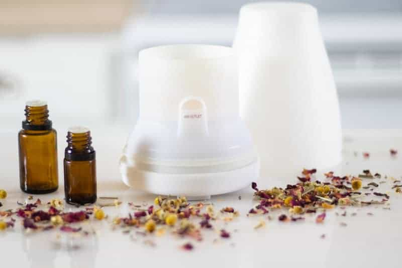 White essential oil diffuser on marble table with dried petals around it.