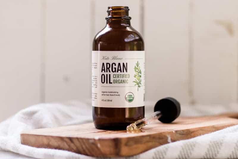 Bottle of argan oil sitting wood cutting board.