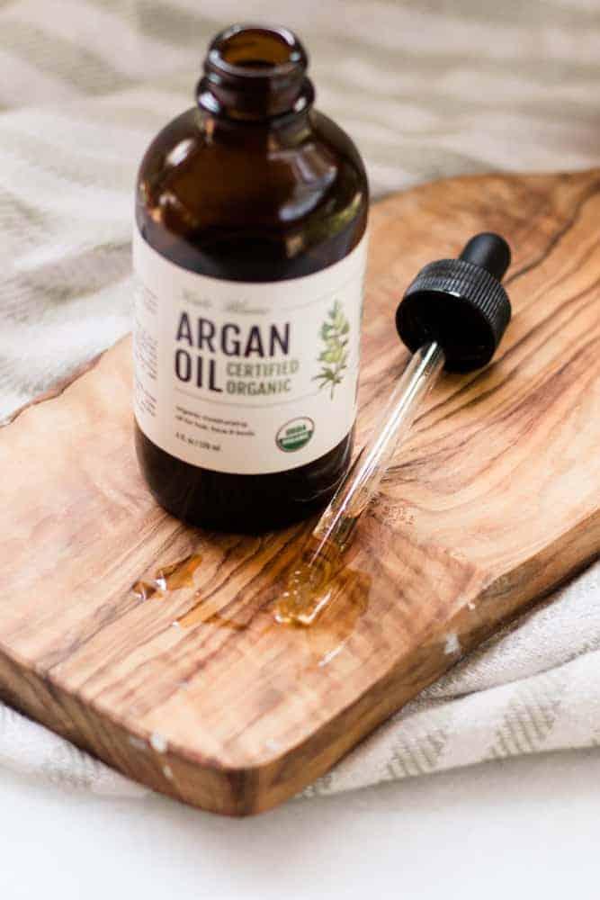 Bottle of open argan oil on wood board.