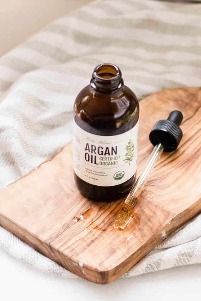 Amber glass bottle of argan oil on wooden cutting board.