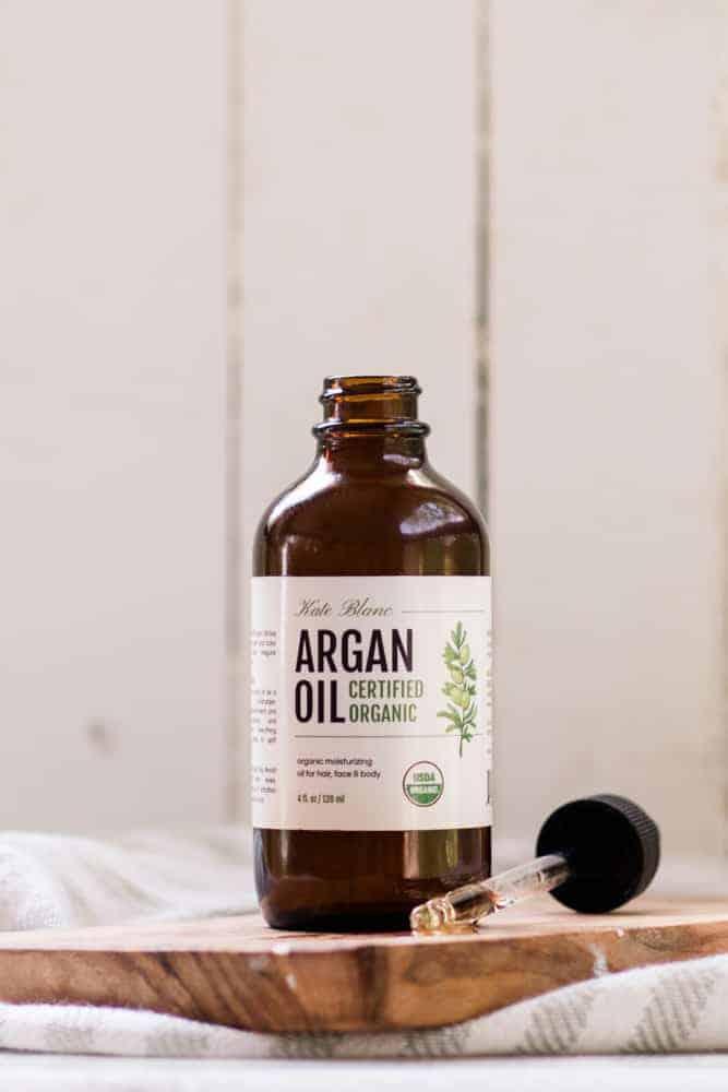 Argan bottle open with dropper of argan oil in front of it.