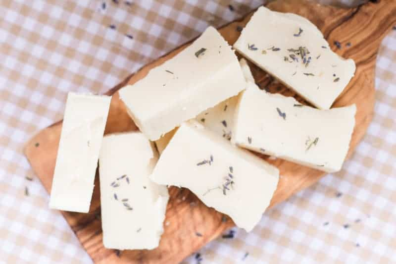 Cold-process soap bars on wooden board with lavender buds.