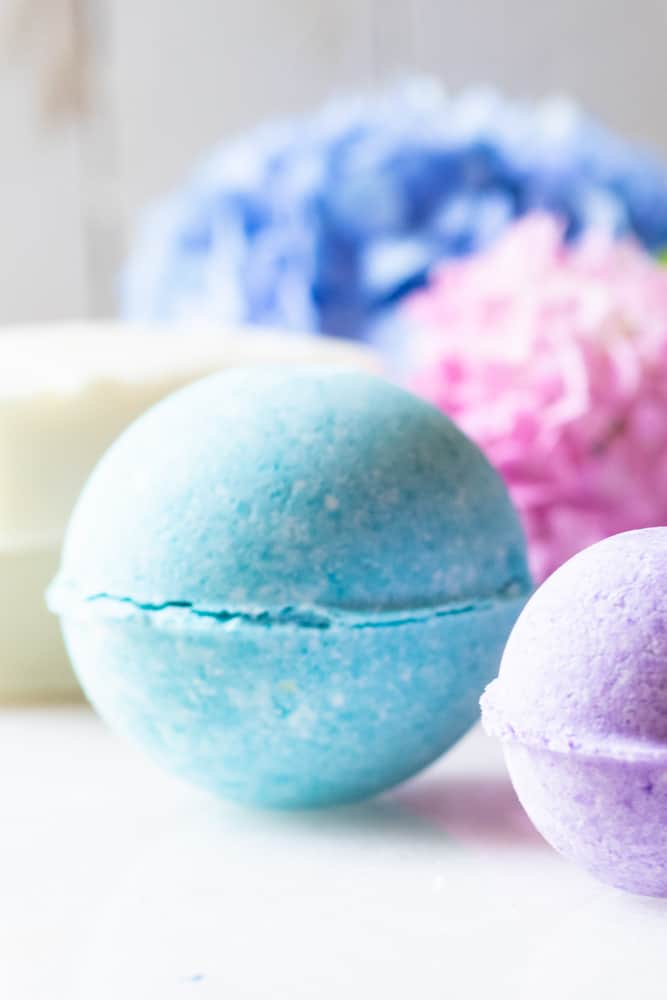 Brightly colored bath bombs with pink and blue flowers behind them.