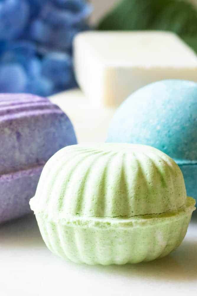 TropIcal bath bombs on white marble table with bright flowers behind them.