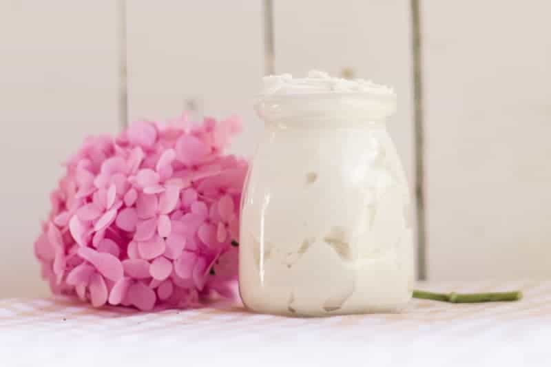 Small glass jar of tallow whipped body butter on table with pink flowers behind it.