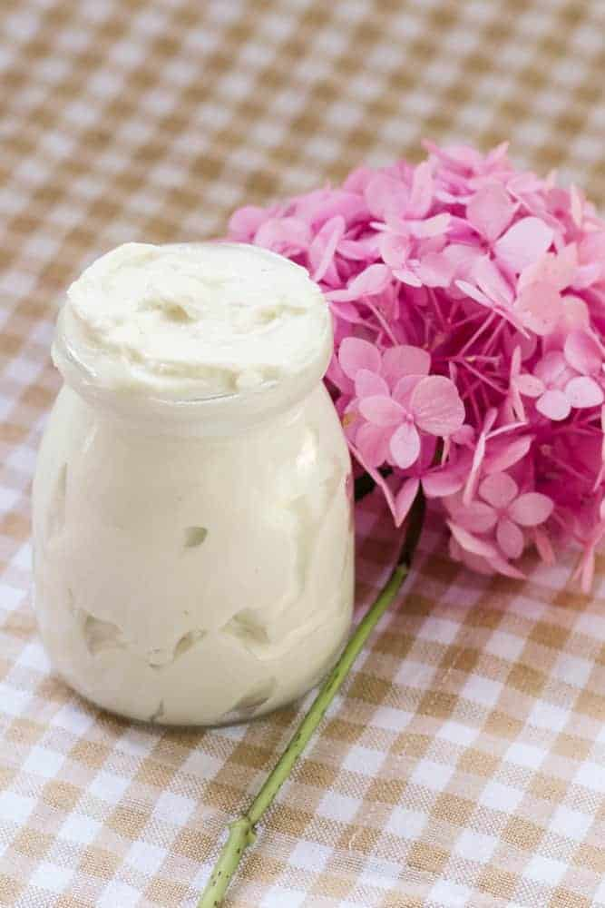 Tallow body butter in glass jar next to pink flowers.