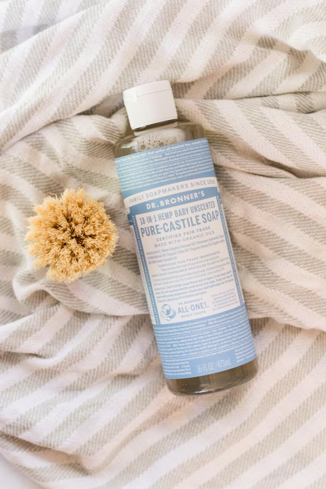 Unscented Castile Soap on white and gray towel with a wood scrub brush next to it.