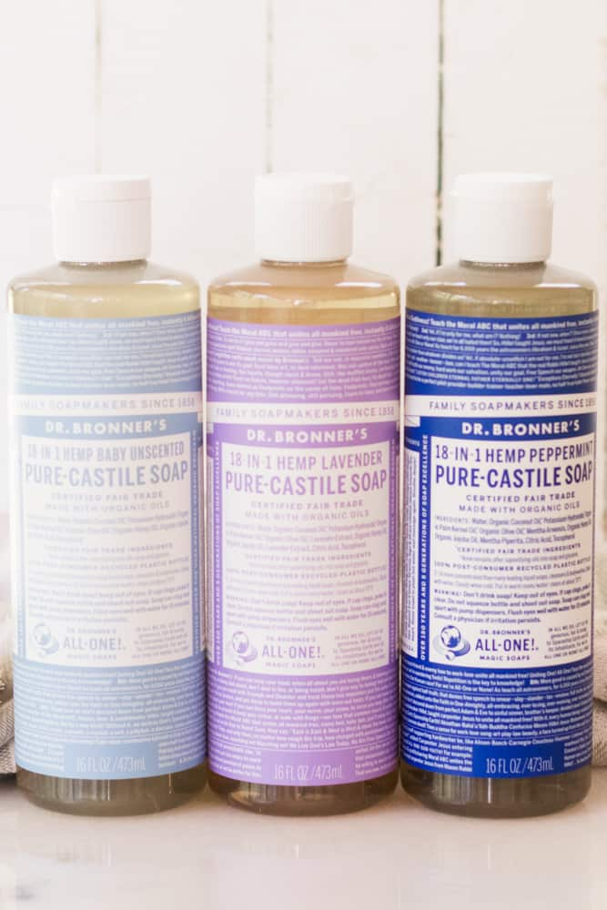Three bottles of Dr. Bronners Castile Soap standing on white marble with white shiplap background.