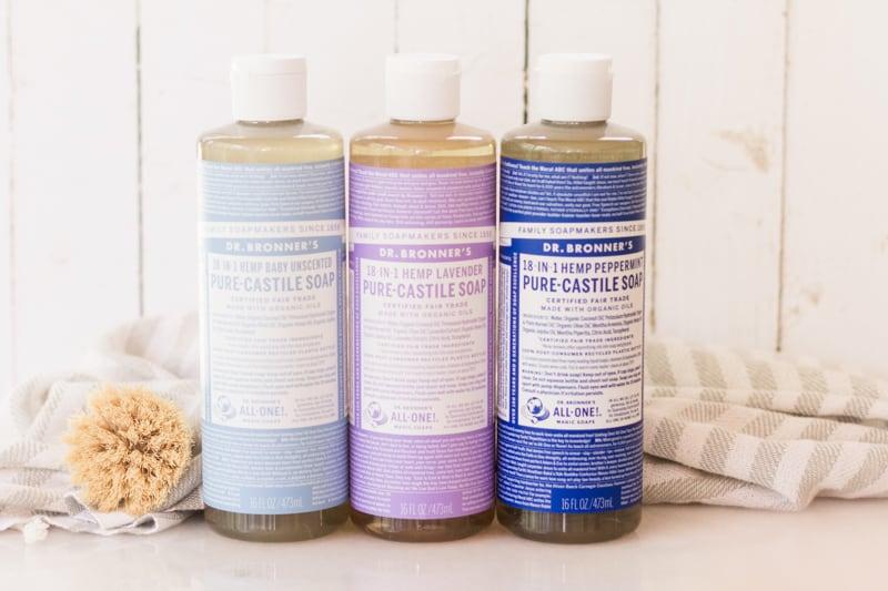 Bottles of castile soap, one light blue, one purple, and one dark blue.