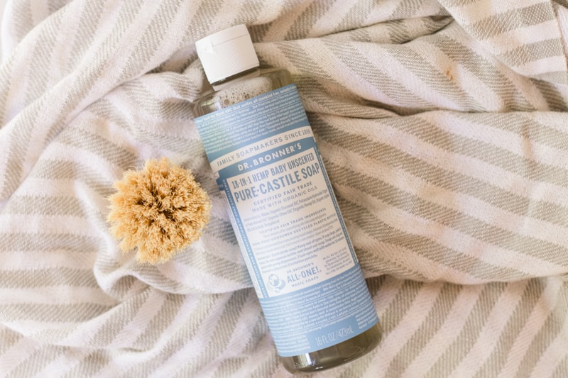 Dr. Bronners Castile Soap on white and gray striped towel.