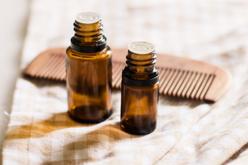 Hair growth essential oil bottles with wooden comb in background.