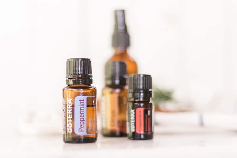 Peppermint, cinnamon, and clove essential oil sitting in front of homemade mouth rinse.