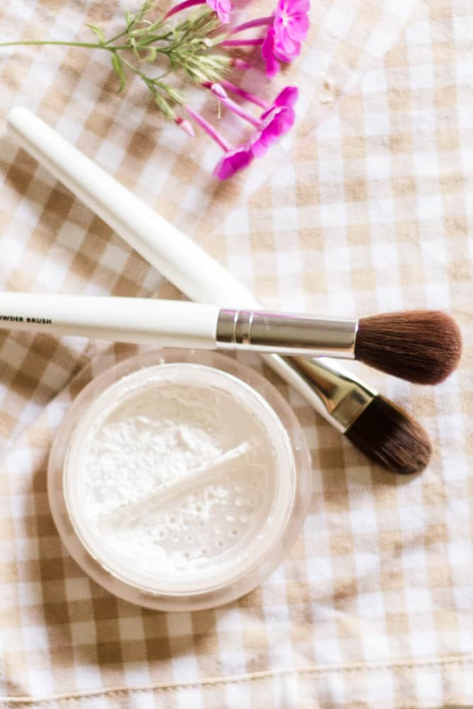 Homemade white setting powder in glass airtight container with 2 makeup brushes.