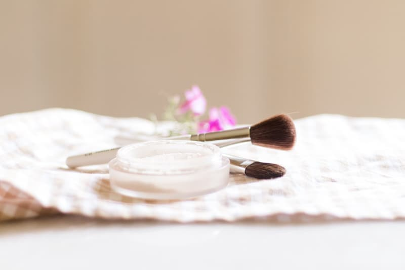 All-natural diy setting powder on white marble with makeup applicator brushes.