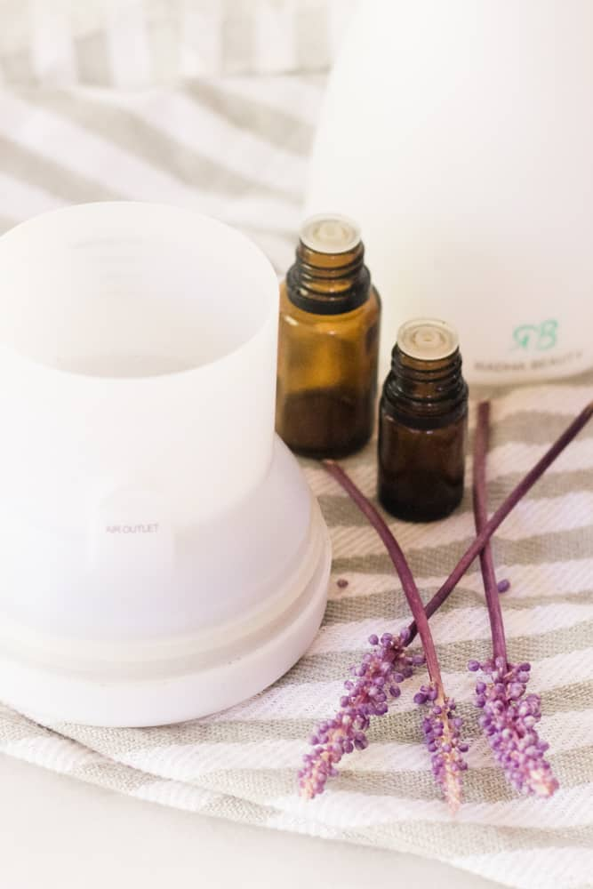 Essential oil diffuser and lavender on white and gray towel.