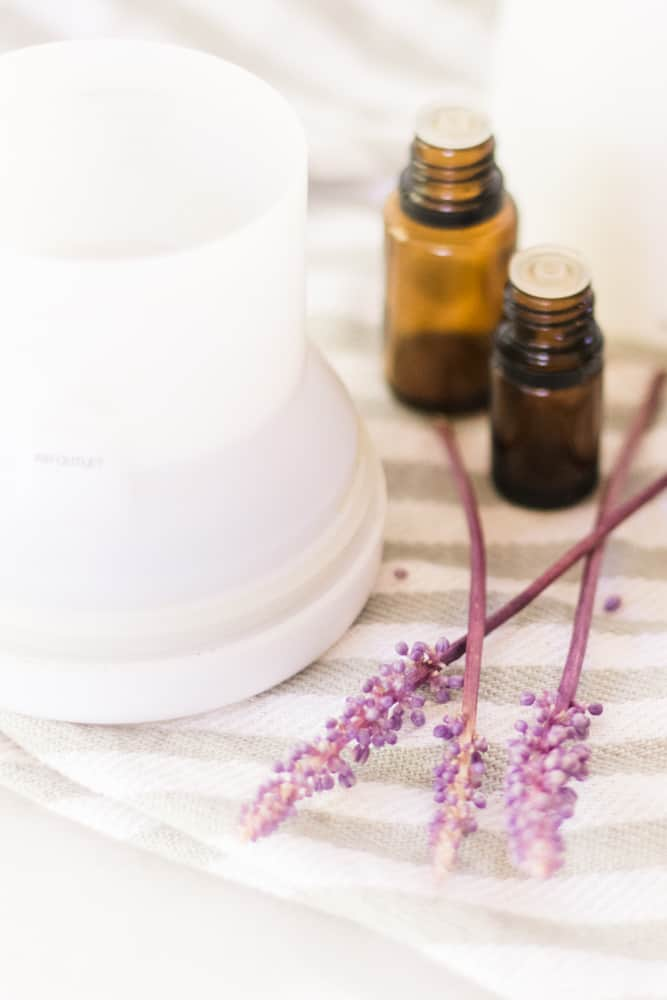 White diffuser with lavender sprigs around it and two amber colored essential oil bottles.