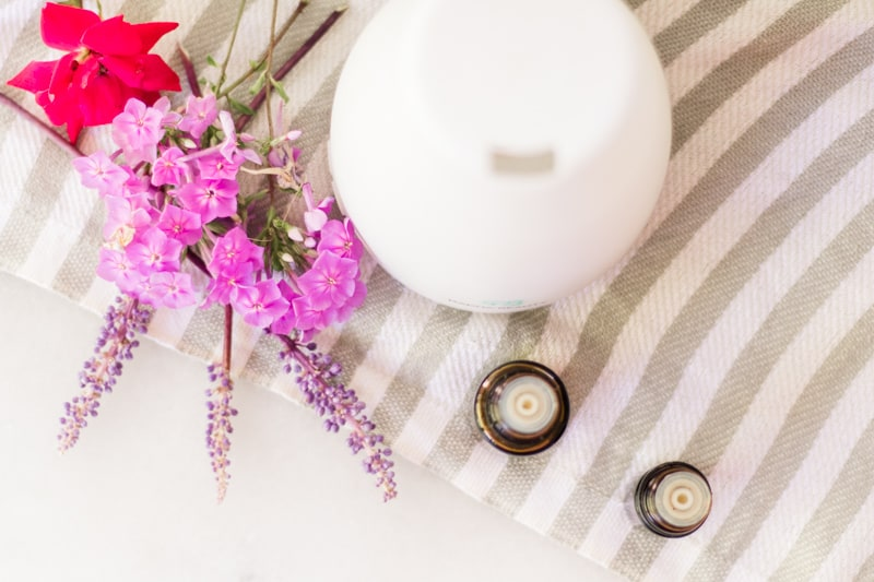 White essential oil diffuser with florals around it.