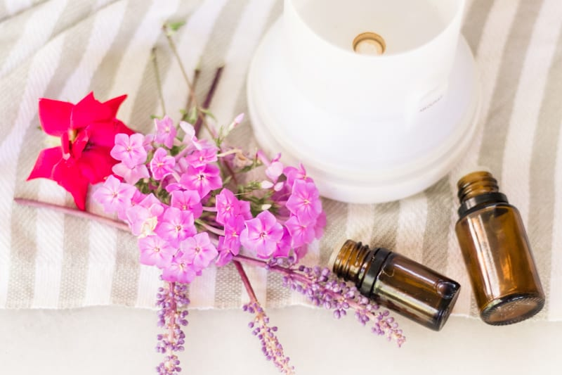 Essential oil diffuser, amber colored essential oil bottles, and flowers on white and gray striped towel.