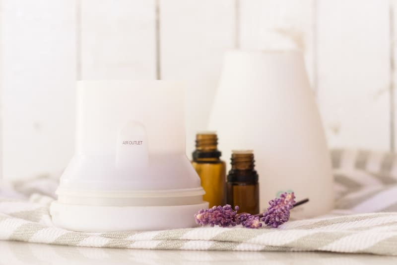 White diffuser on white marble table and lavender sprigs by it.