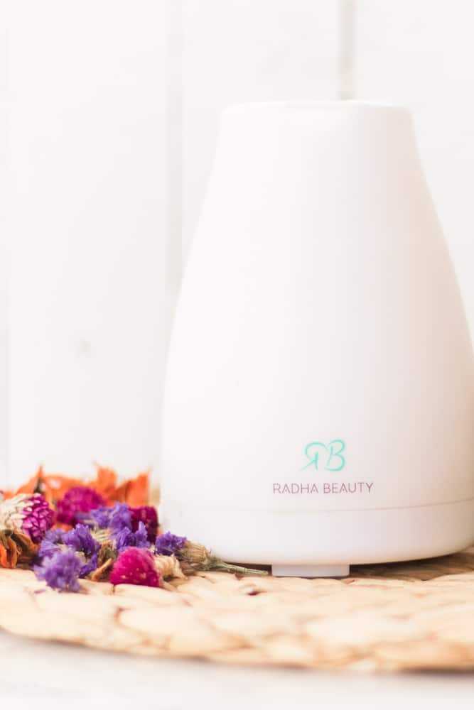 White diffuser with bright flowers next to it.