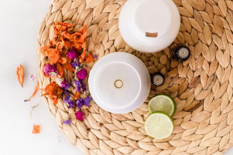 Diffuser with bright flowers and lime slices around it.