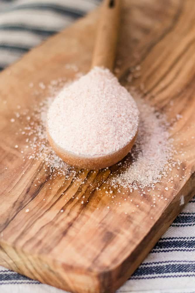 Pink Himalayan salt spilling out of wooden measuring spoon.
