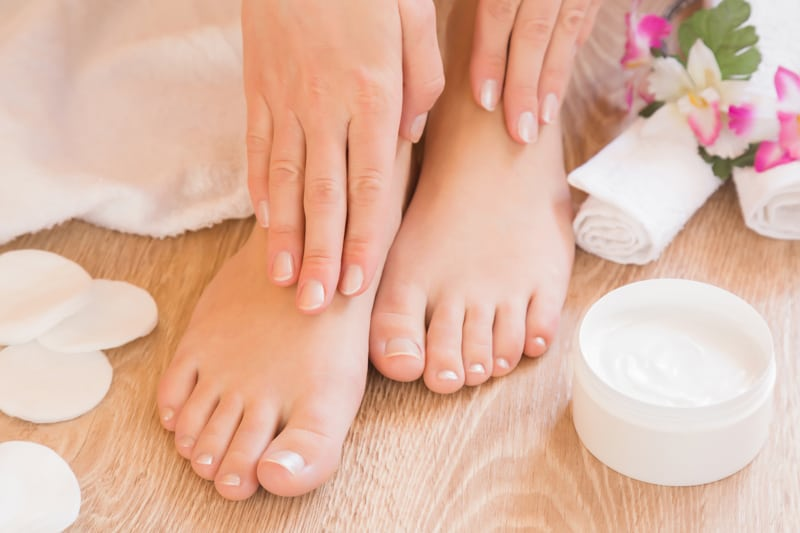 Women feet and hands with lotion and flowers by them.