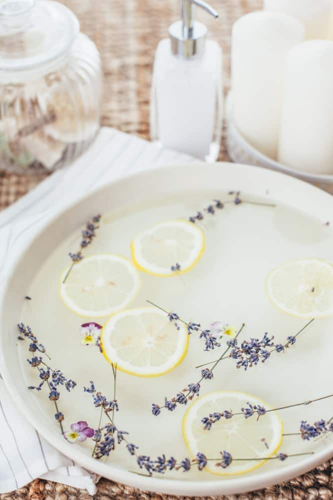 White bowl of at home foot soak with lemon slices and dried lavender.
