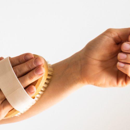 hand with dry brush brushing arm