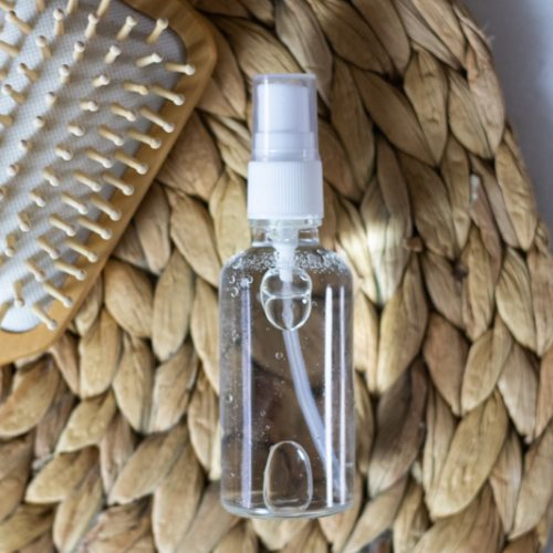tan hair brush and glass spray bottle with essential oil hair spray